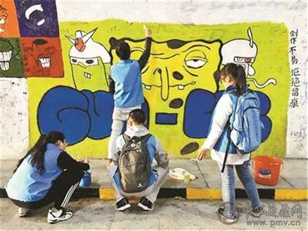 厦门大学学生在修复被游客涂鸦的墙面.jpg
