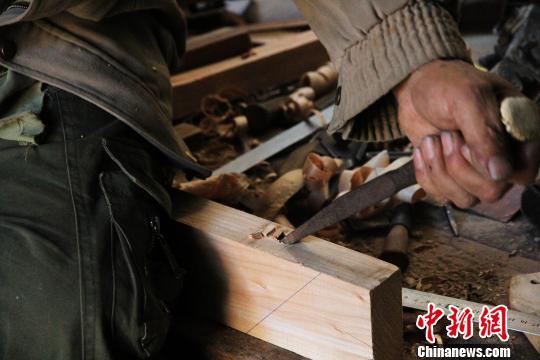 5月4日,在历城明式传统家具制作技艺第六代传人徐光祥家中,徐光祥正在为桌案板凿卯眼。 郝学娟 摄