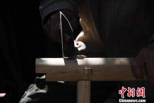 据了解,徐光祥已掌握30余种榫卯结构制作技艺。图为徐光祥组合榫卯结构桌腿。 郝学娟 摄