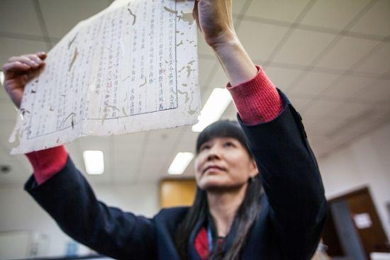 上海图书馆文献保护部主任张品芳正在修复古籍善本