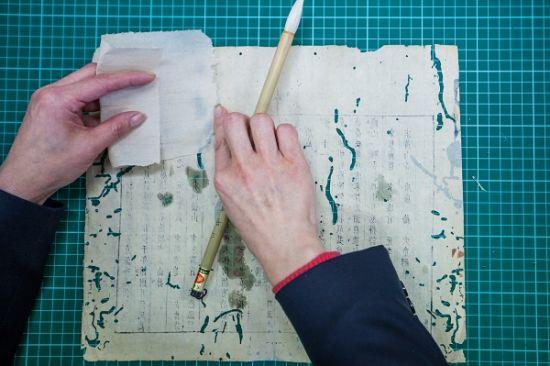 古籍修复人员对书页破洞进行修补